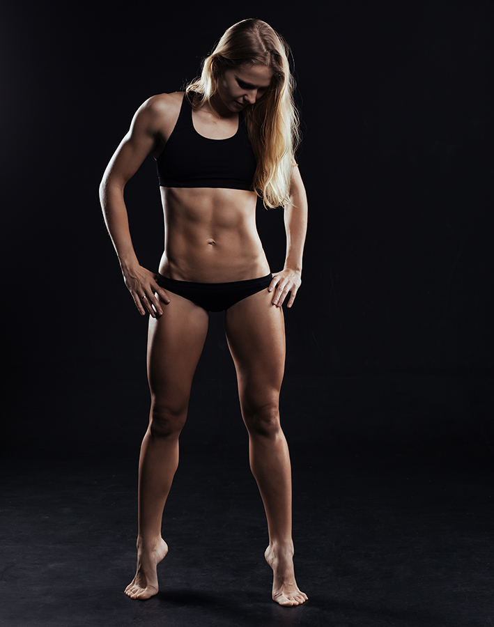 Sport fitness woman with strong muscles on black background